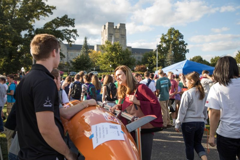 Dean Ross listens to engineering students at GobblerFest talk about their submarine project on the Drillfield fo Virginia Tech on an early fall day