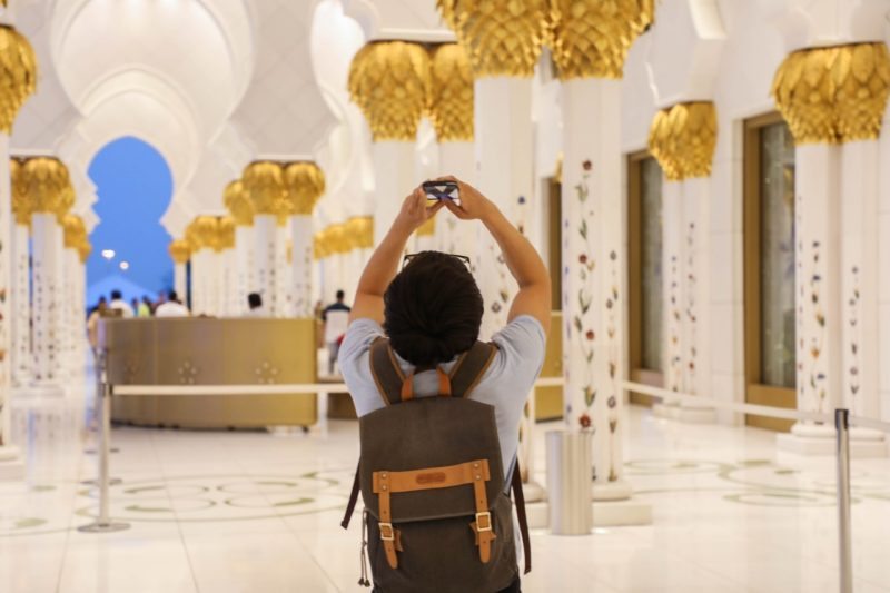 A student taking a picture of the ceiling in an ornate marble and gold interior