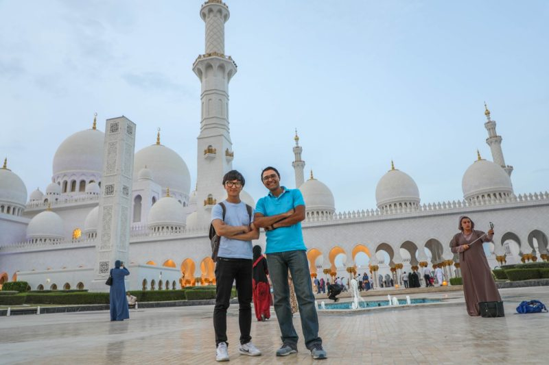 Two students stand smiling side-by-side, arms crossed, in front of the Grand Mosque in Abu Dhabi, which is tall, white, and topped with oval steeples.