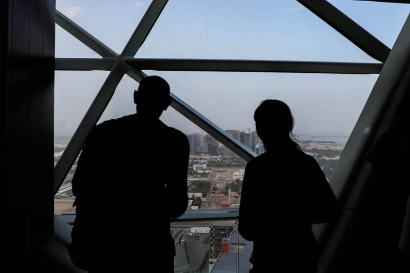 Two students looking out the window of a tall building overlooking the city