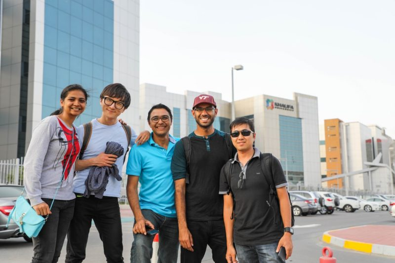 Group of five students posing for a photo in the city