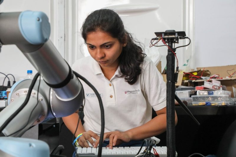 Urvi Desai, a student, works on a ground vehicle. She is using a mouse and keyboard and focusing intently on the equipment.