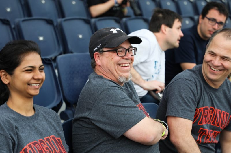 "Three people wearing gray shirts that read ""Virginia Tech"" in orange and maroon laugh together while sitting in blue stands."