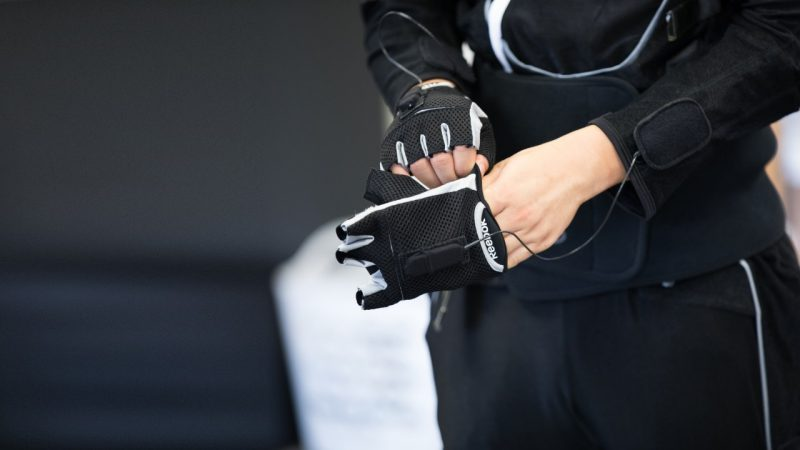 Close up of hands as a person in the black, and wired motion, suit puts on fingerless gloves that are part of the suit.