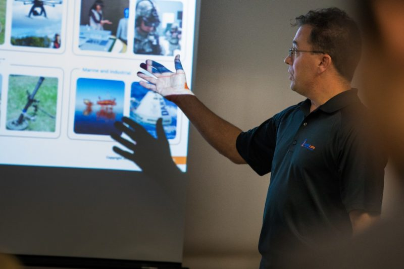 Jamie Marraccini gestures to a slideshow on a screen behind him in a darkened room.