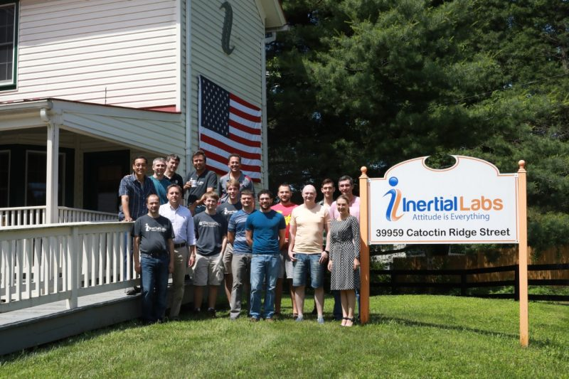 Employees of Inertial Labs gather outside of their office building for a group shot by their sign.