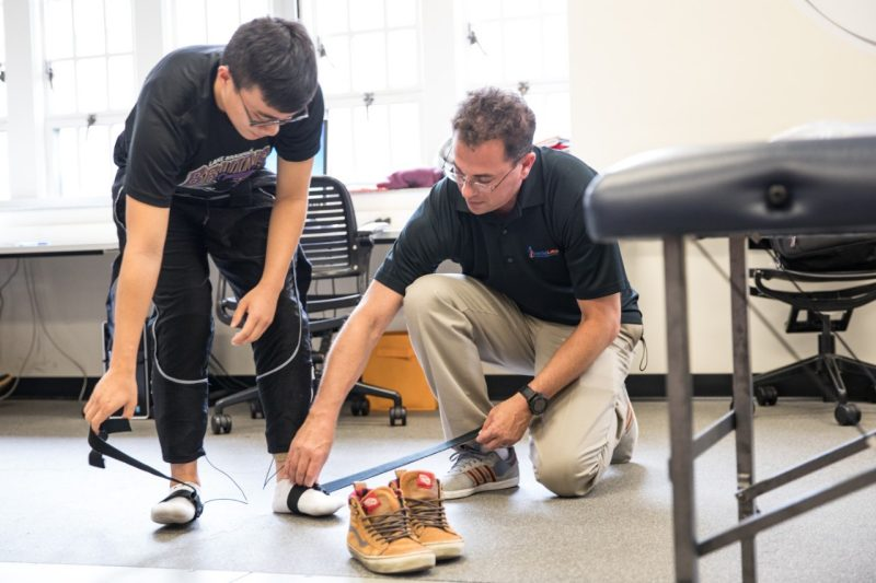 Jamie Marraccini, a class of '93 graduate, helps a Virginia Tech student strap sensors to his feet