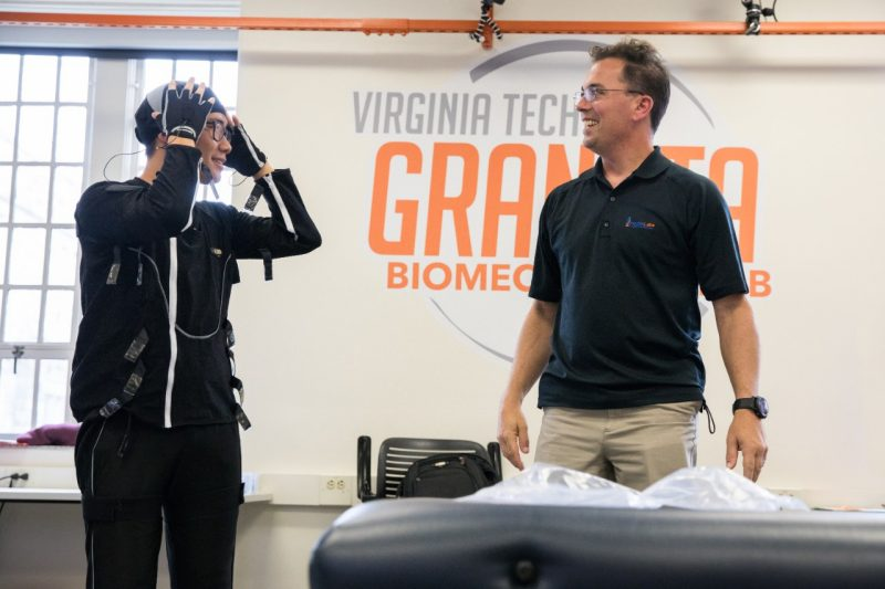 A student, wearing a motion capture suit, smiles at Jamie Marraccini, standing nearby.