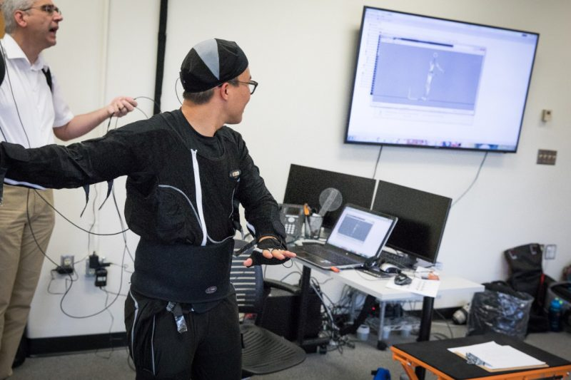 A student wearing a motion capture suit looks on at the screen where his movements are being translated into a digital stick figure representation of him.