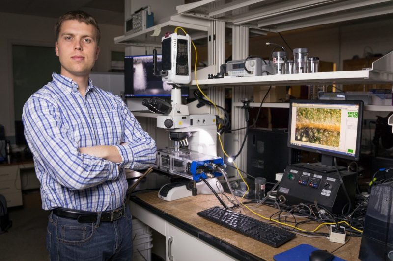 Jonathan Boreyko stands in a lab with his arms crossed in front of a microscope.