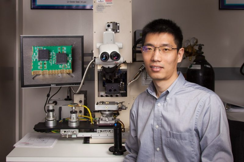 Qiang Li in front of his lab microscope